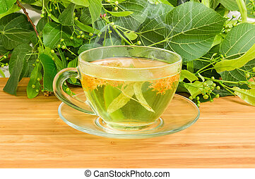 Linden tea in glass cup against of fresh linden branches