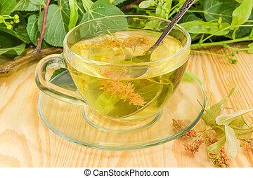 Linden tea in glass cup and dried linden flowers closeup