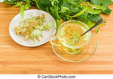Linden tea in glass cup and dried linden flowers