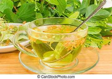 Linden tea in transparent glass cup with tea spoon closeup