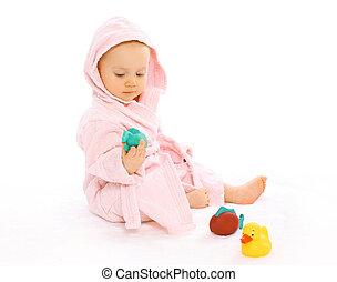 lindo, bebé, en, albornoz, juego, con, agua, caucho, juguetes