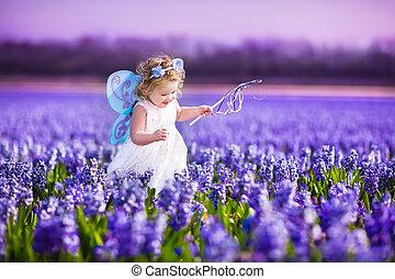 lindo, bebé, niña, en, traje de hada, en, un, flor, campo