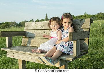 lindo, hermana, ellos, sentar banco, en, sunset.