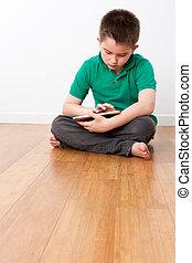 lindo, macho, niño, sentado sobre el piso, con, tableta