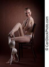 lindo, mujer desnuda, en, silla, sonrisa, desvestir, sostén
