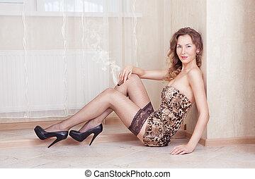 lindo, mujer, mentira en el piso, fumar, un, cigarro, medias, y, vestido de leopardo