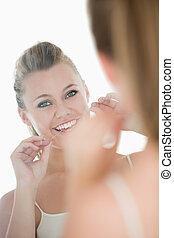 lindo, mujer, utilizar, seda dental, delante de, espejo