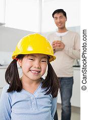 lindo, niña, en, sombrero duro amarillo, con, padre, en, plano de fondo