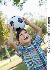 lindo, niño joven, juego, con, pelota del fútbol, aire libre, en, el, park.