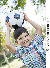 lindo, niño joven, juego, con, pelota del fútbol, en el estacionamiento