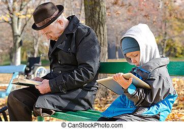 lindo, niño joven, lectura, un, libro electrónico, en, un, tableta