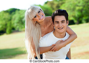 lindo, pareja, piggybacking, outdoors.