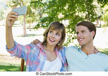 lindo, pareja, sentar banco, en el parque, toma, un, selfie