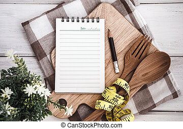 Line Notepad on chopping board with wooden fork and spoon and the measuring tape on white table , recipes food or diet plan for healthy habits shot note background concept