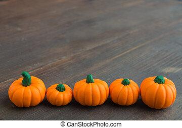 Line of artificial pumpkin on wooden background