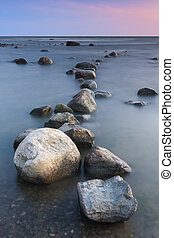 Line of bigh rocks in sea at sunset