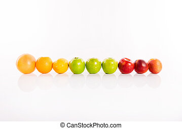 Line of bright fruits on white background