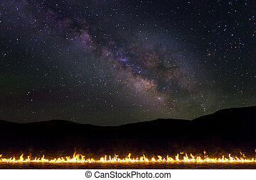 Line of Burning Fire in the desert with milky way