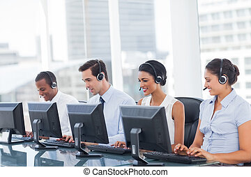Line of call centre employees working on computers