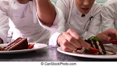 Line of chefs garnishing dessert pl