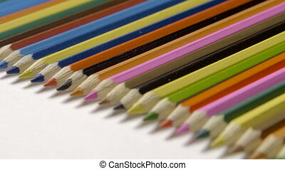 Line of colour pencils isolated on white background close up