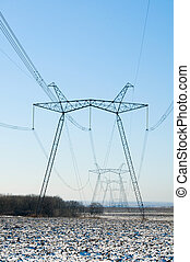 Line of electric pylons on winter field
