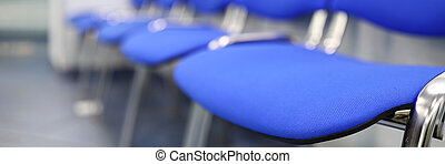 Line of empty blue visitor chairs at reception or in bank