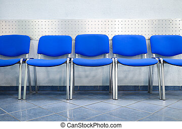 Line of empty blue visitor chairs standing near wall at reception or in bank
