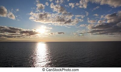 line of horizon dividing sea and sky with sun and clouds