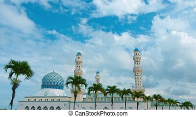 UltraHD video - Timelapse shot of Kota Kinabalu City Mosque on the island of Borneo, in Malaysia, with clouds drifting by and palm trees swaying in the foreground.