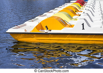 line of pedal boats on a pier, row of boats - line of pedal...