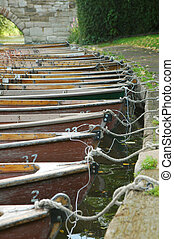 rowing boats - line of wooden rowing boats tied to a river ...