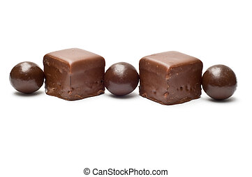 Lined chocolate balls and cubes side view
