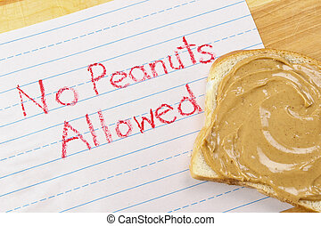 """Lined primary school paper with """"No Peanuts Allowed"""" written in red crayon warns against peanut products which are dangerous food allergens"""