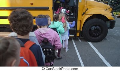 Lined up elementary age kids boarding school bus - Back view...