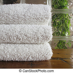 Clean white bath towels framed by glass block