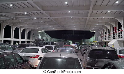 Lines of cars loaded inside a car and passenger ferry boat crossing Kerch strait