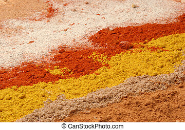 Lines of different spices - from front to back: cinnamon, ...