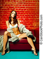 Lingerie and fur - Sexy lingerie female model on red sofa