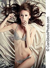 Lingerie - Beautiful lady in lingerie lying in bed of silk...