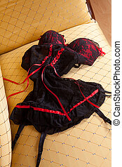 Lingerie on the sofa - Sexy red and black corset on a satin ...