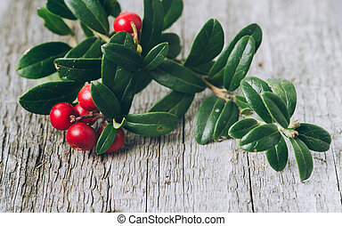 Lingonberries with leaves on a wooden background