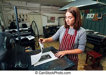 girl prints linocut on the machine