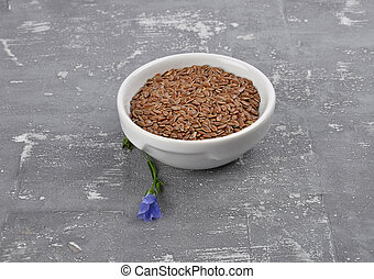 Linseed and common flax in bowl on concrete