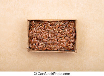 Linseed in carton on brown background
