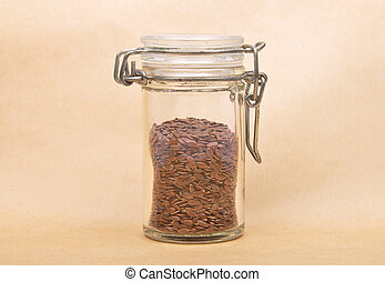 Linseed in glass on brown background