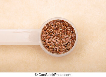 Linseed in measuring spoon on brown background