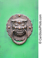 Lion-shaped door knocker on a green door in Beijing, China