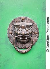 Lion-shaped door knocker on a green door in Beijing, China