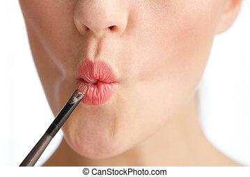 Close up portrait of a half face young woman with lip gloss make up application